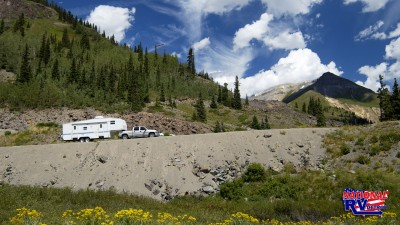 Truck driving up mountainside with fifth wheel