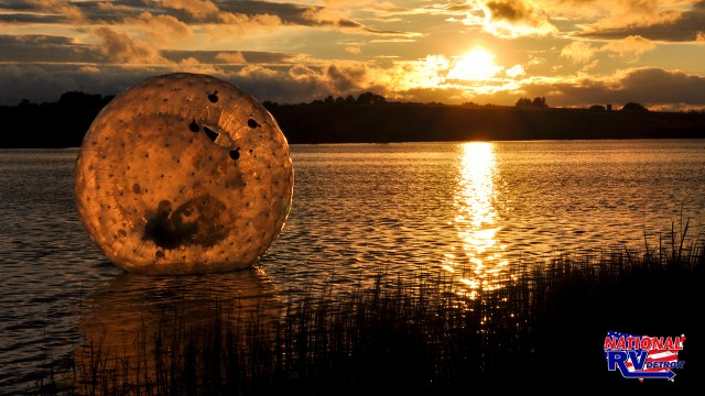 Zorbing  floating in the lake at sunset
