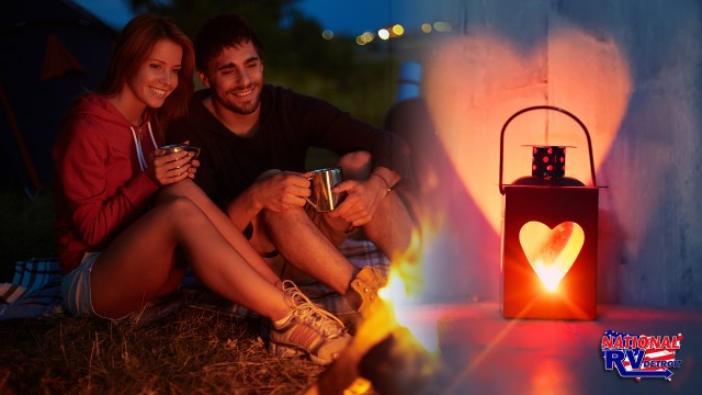 A couple camping and a heart shaped lantern