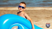 Little boy holding floaty at WJ Hayes State Park Beach