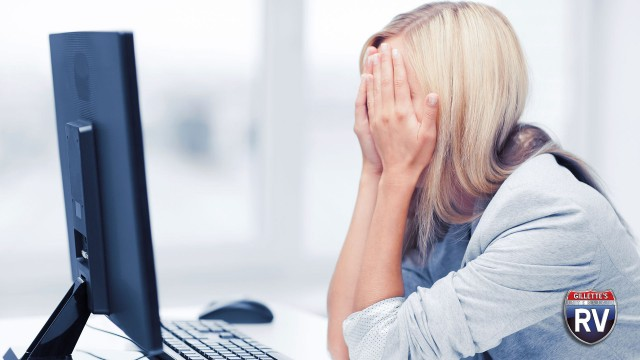 Frustrated Woman Sitting At Computer With Hands Over Face