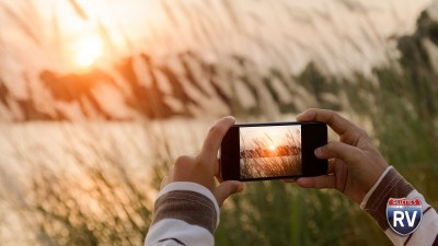 Person Taking A Photo With Their Phone Of The Sunrise Over Lake