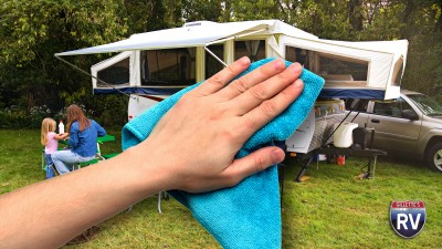 Hand With Cleaning Rag And Family With Pop Up Camper
