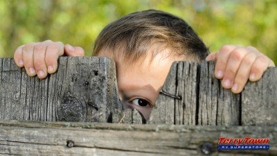 Kid peeping through wooden fence