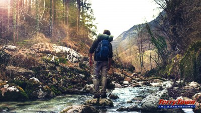 man backpacking through the woods crossing a river