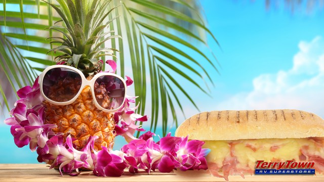 Pineapple with sunglasses and lei next to ham sandwich with palm tree