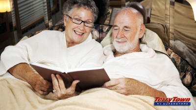 older couple in RV bed reading