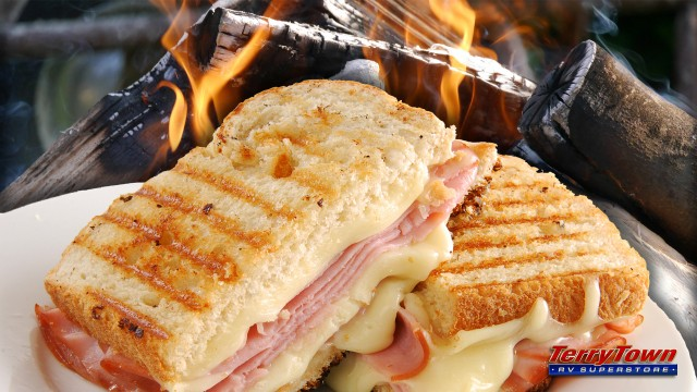 Melted cheese and ham sandwich with a campfire in the background.