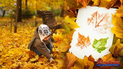 young boy picking up fall leaves to use for leaf printing