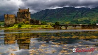 Castle in Scotland on lake with mountains in the background