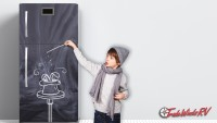 Boy drawing with chalk on kitchen fridge.