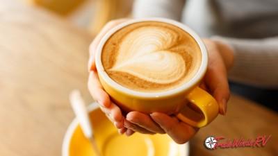 holding coffee mug with foam heart