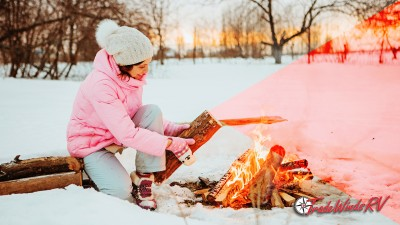 Woman making a campfire in winter.