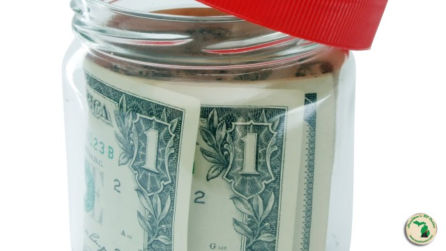 Dollar Bills Wrapped Up In Clear Jar