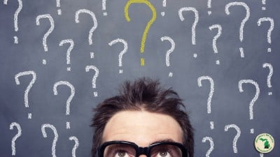 Man looking up with many question marks above his head