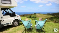 Couple overlooking hills and fields to the ocean in fold away chairs Feature