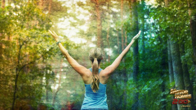 Woman In Workout Clothes With Arms Raised In Forest