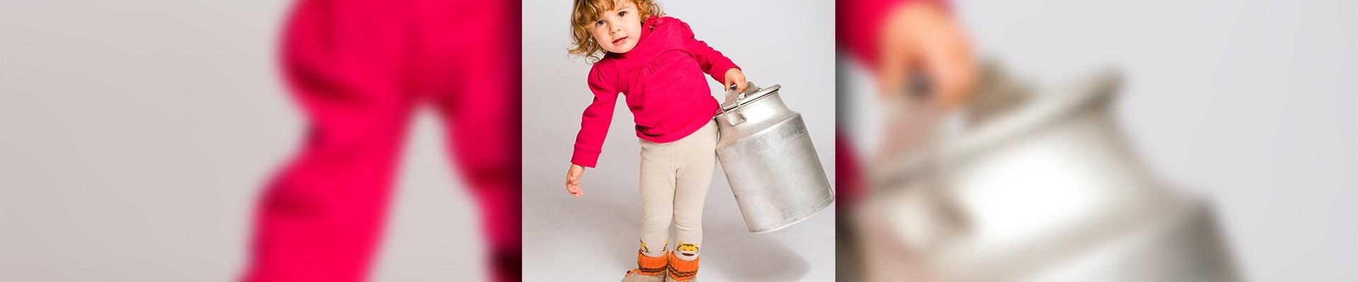 little girl lifting a milk jug