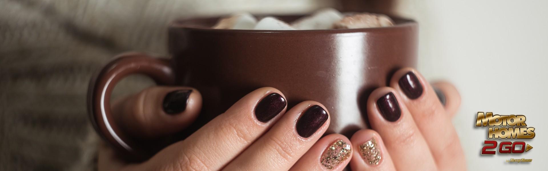 Girl with holiday nail polish holding hot chocolate