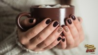 Girl with holiday nail polish holding hot chocolate