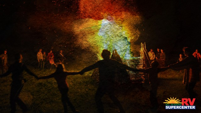 Group Of People Dancing Around Rainbow Colored Bonfire