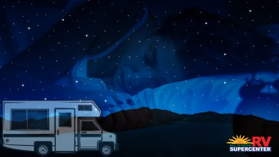 An RV Parked Under The Stars With Woman Sleeping In Background