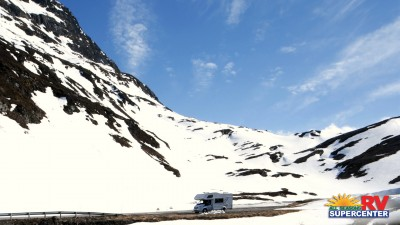 RV Driving Through The Snowy Mountains